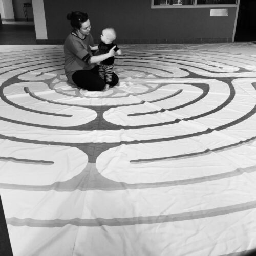 a mother and child sit in the middle of the Labyrinth