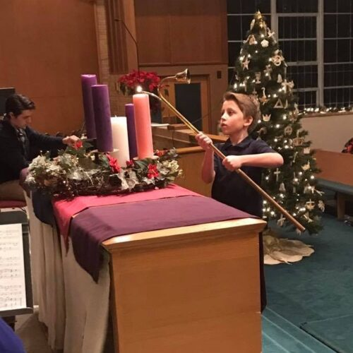 Alex Byrd lights the candle of Hope during Advent