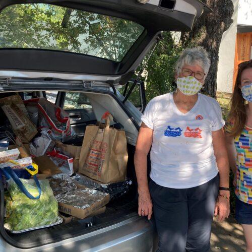 Kelley DeCleene and Alana Mallard in front of food donations