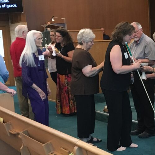 Pastor and lay members serve communion