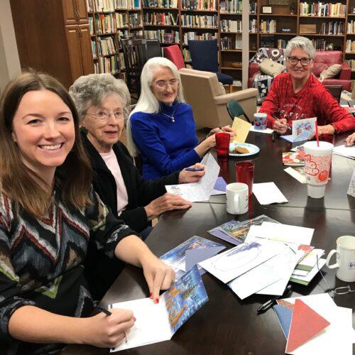 Ladies write Christmas cards to homebound members