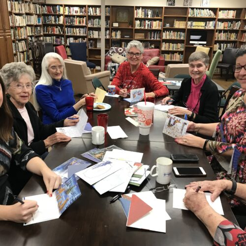 Ladies write Christmas cards to homebound members