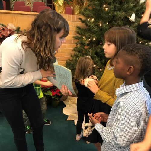 Abby Byrd speaking to children in front of Christmas tree