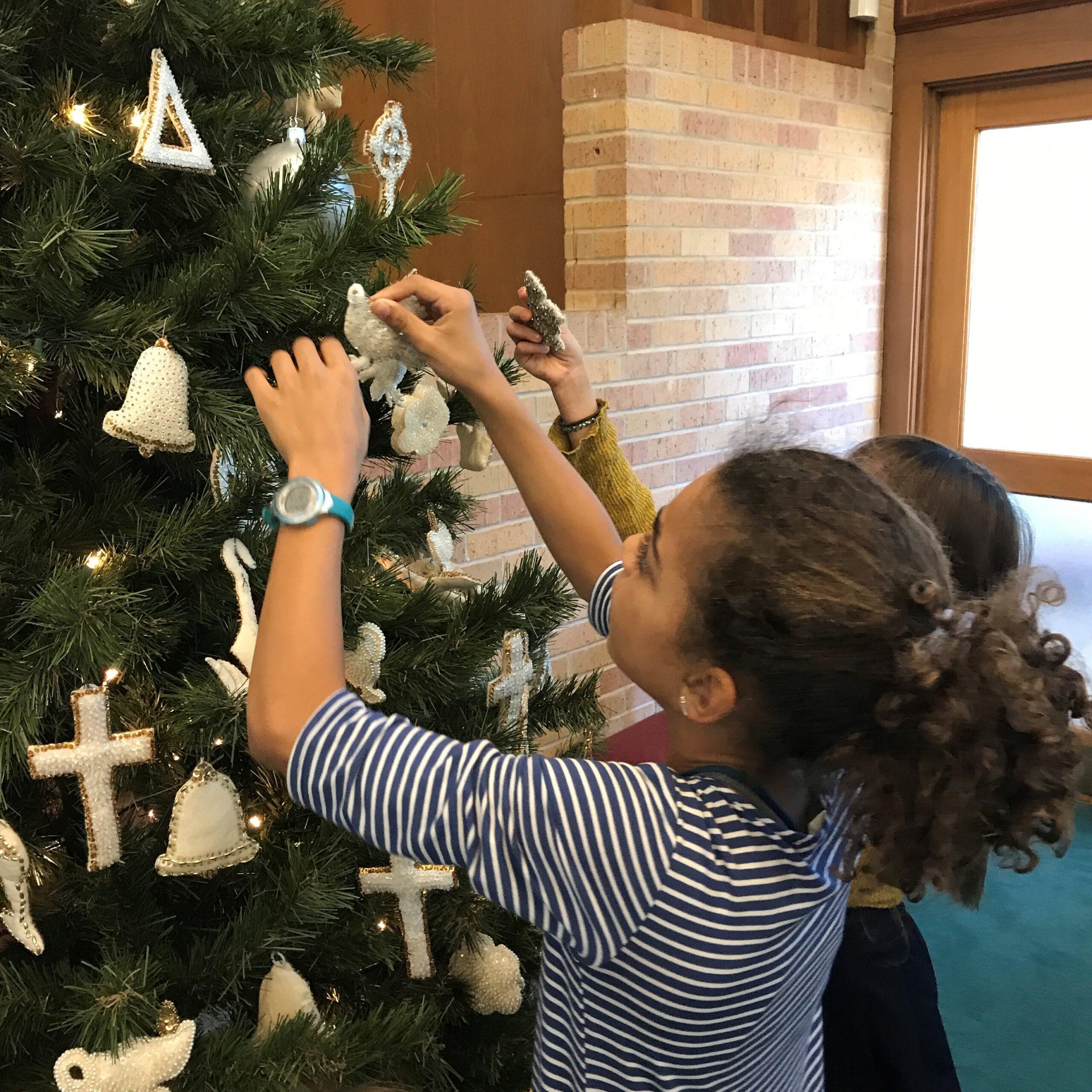 Bell Morton puts Chrismon on Sanctuary Christmas tree