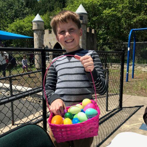 Alex Byrd with full basket at Palm Sunday Picnic & Easter Egg Hunt