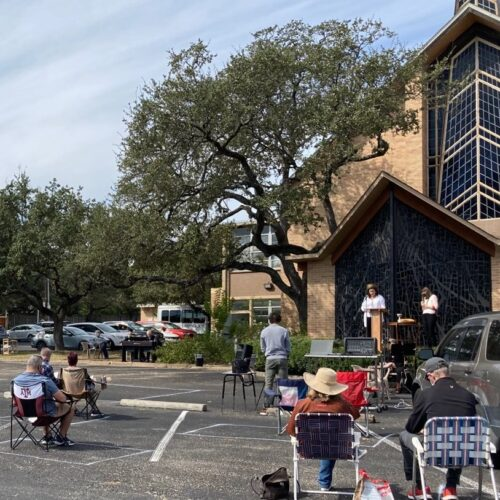 Worshippers sit outdoors as staff leads outdoor worship