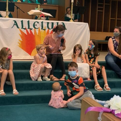 the kids listen to the children's sermon from Abby Byrd on the altar steps